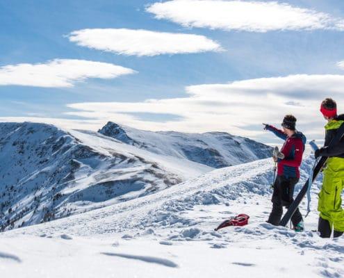 Skitourengeher beim Auffellen mit Panoramablick zum Königstuhl auf der Nockberge-Trail Skidurchquerung