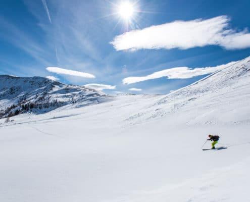 Skitourengeher beid er Abfahrt Grünleitenscharte auf der Nockberge-Trail Skidurchquerung mit Blick auf die Nockberge