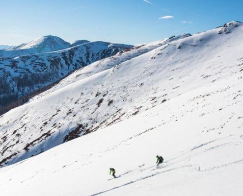 Skitourengeher bei der Abfahrt Richtung Hundsfeldhütte mit Blick auf die Nockberge