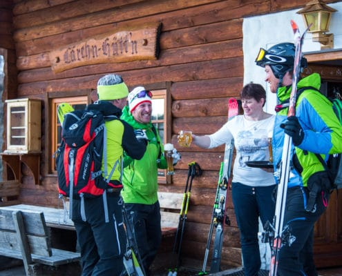 Skitourengeher bei einer Stärkung vor der Lärchn-Hüttn auf der Nockberge-Trail Skidurchquerung