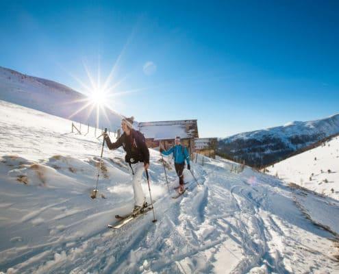 Skitourengeher vor den Hundsfeldhütten auf der Nockberge-Trail Skidurchquerung